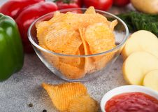 Glass bowl plate with potato crisps chips with paprika on light table background. Red and green paprika pepper with potatoes and. Glass bowl plate with potato stock images