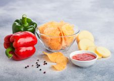 Glass bowl plate with potato crisps chips with paprika on light table background. Red and green paprika pepper with potatoes and. Glass bowl plate with potato royalty free stock photo