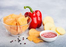 Glass bowl plate with potato crisps chips with paprika on light table background. Red paprika pepper with potatoes and sweet. Glass bowl plate with potato crisps royalty free stock images