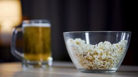 Glass bowl of popcorn and beer standing on table at home, lazy night at home. Stock footage Stock Photography