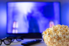A glass bowl of popcorn, 3d glasses and remote control in the background the TV works. Evening cozy watching a movie or TV series. At home stock image