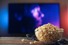 A glass bowl of popcorn, 3d glasses and remote control in the background the TV works. Evening cozy watching a movie or TV series. At home royalty free stock image
