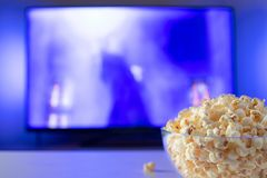 A glass bowl of popcorn and remote control in the background the TV works. Evening cozy watching a movie or TV series at home.  royalty free stock image