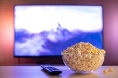 A glass bowl of popcorn and remote control in the background the TV works. Evening cozy watching a movie or TV series at home.  stock photography