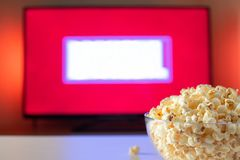 A glass bowl of popcorn and remote control in the background the TV works. Evening cozy watching a movie or TV series at home.  royalty free stock photography