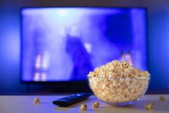 A glass bowl of popcorn and remote control in the background the TV works. Evening cozy watching a movie or TV series at home.  royalty free stock images