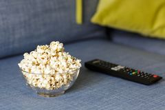 A glass bowl of popcorn and remote control. Evening cozy watching a movie or TV series at Home stock image