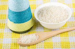 Glass bowl with rice, bottle of oil and wooden spoon Royalty Free Stock Images