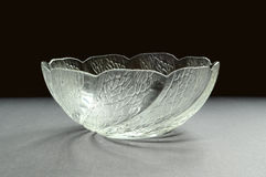 Glass bowl with sculpture pattern. A glass bowl decorated with sculpture pattern casts a spiral shadow Stock Photos