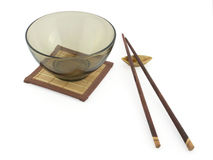 Glass bowl and shopsticks. Glass bowl on little bamboo-mat and shopsticks stock images