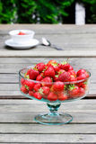 Glass bowl of strawberries on wooden garden table Royalty Free Stock Photos
