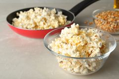 Glass bowl with tasty popcorn on grey table. Space for text stock photo