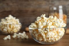 Glass bowl with tasty popcorn on table. Space for text royalty free stock photos