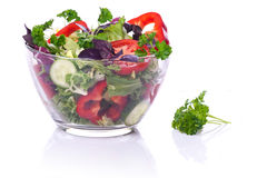 Glass bowl with vegetables for a salad. Glass bowl with vegetables for a salad on a white background with reflection Royalty Free Stock Image