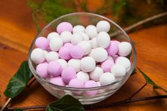 Glass bowl with white and pink sugared almonds. Arranged for the guests at the reception stock photo