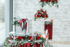 Glass box on round table covered with red  cloth, roses and gree Royalty Free Stock Photos