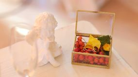 Wedding rings in a glass box with Rowan berries. Glass box with Rowan berries and wedding rings on the table, next to the statue of the angel. Wedding decor stock video footage