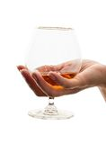 Glass of brandy. Woman's hand with glass of brandy on white background Royalty Free Stock Photo