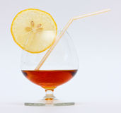 Glass of brandy. Concept image of brandy glass with a lemon segment and a straw Stock Photo