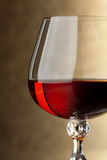 Glass of brandy. Macro shooting with a glass of brandy on a golden background. Fragment royalty free stock photo