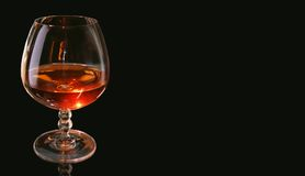 Glass of a brandy. On a black background Royalty Free Stock Images