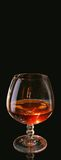 Glass of a brandy. On a black background Stock Photos