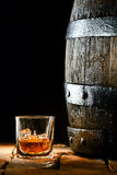 Glass of brandy alongside an oak barrel. Glass of golden matured premium brandy or whiskey on the rocks alongside an old oak barrel standing upright on old Stock Photography