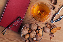 Glass of brandy a book and nut selection Stock Photo