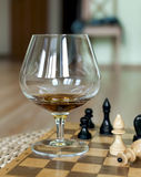 Glass from a brandy and chess Royalty Free Stock Photo