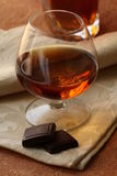 Glass of brandy and chocolate Stock Images