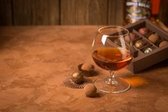 A glass of brandy and chocolate candy on a dark background. Alcoholic drink and elite chocolate still life. Copy space. royalty free stock photography