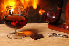 A glass of brandy, chocolate and tobacco pipe  on the background Royalty Free Stock Photo