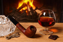 A glass of brandy, chocolate and tobacco pipe  on the background Stock Image