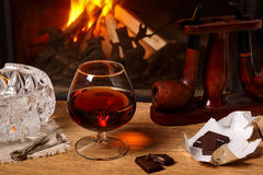 A glass of brandy, chocolate and tobacco pipes  on the backgroun Royalty Free Stock Images