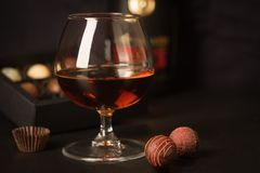 A glass of brandy and chocolates in a paper box. Alcoholic drink on a dark background. Selective focus. stock image
