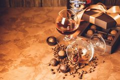 A glass of brandy and chocolates in a paper box. Alcoholic drink on a dark background.Selective focus. stock photography