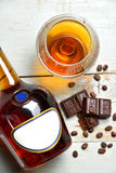 Glass of brandy cognac on a old wooden table with chocolate coff Royalty Free Stock Photography