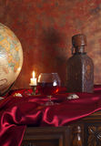 Glass of brandy and globe on an antique table Stock Images
