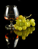 Glass of brandy and grapes Royalty Free Stock Image