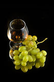 Glass of brandy and grapes Royalty Free Stock Images