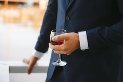 A glass of brandy in the hands of the groom royalty free stock photography