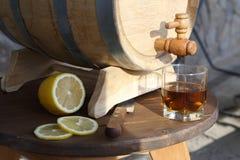 Brandy with lemon near oak barrel on a wooden table. A glass of brandy near an oak barrel with lemon on a wooden table stock images