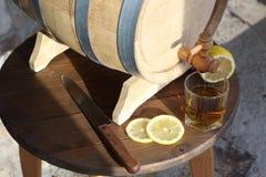 Brandy with lemon near oak barrel on a wooden table. A glass of brandy near an oak barrel with lemon on a wooden table stock photography