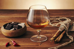 Glass of brandy. On a old wooden table with a bowl with chocolate, cinnamon stiks and chili peppers. Warm background Stock Photos
