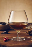 Glass of brandy. On a old wooden table with a bowl with chocolate, cinnamon stiks and chili peppers. Warm background stock images