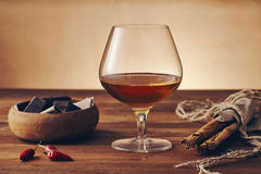 Glass of brandy. On a old wooden table with a bowl with chocolate, cinnamon stiks and chili peppers. Warm background Stock Photo