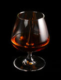 Glass of brandy over black Stock Photo