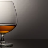 Glass of brandy over grey background Royalty Free Stock Images