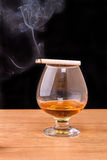 Glass of brandy and smoking a cigarette Royalty Free Stock Images