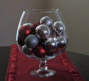 Glass brandy snifter with red and silver sparkles royalty free stock photos